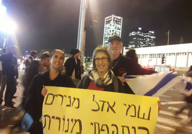 Residents of the South hold up a poster at a ceasefire protest in Tel Aviv.