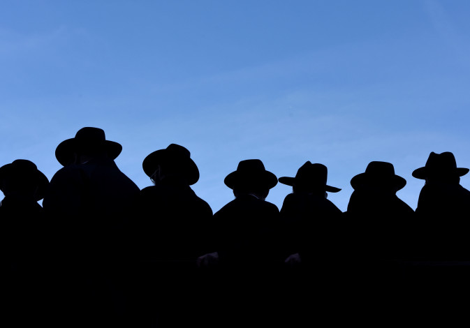 Rabbis hats are silhouetted against the sky as they gather to pose for a group photo in front of the
