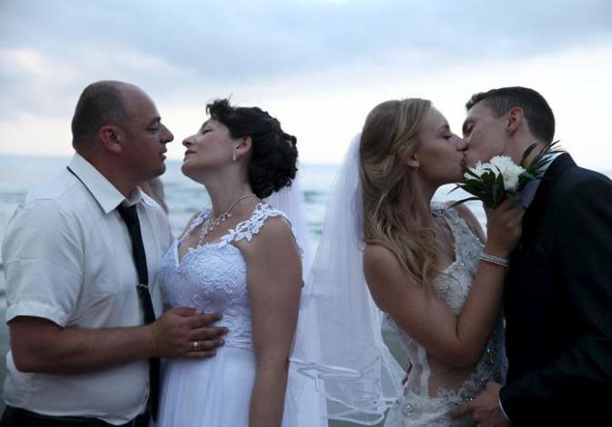 Couples kiss during a mass wedding at coastal city of Larnaca