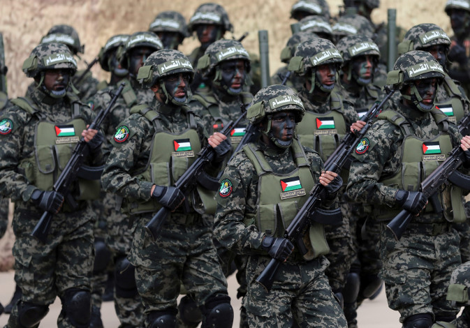Palestinian Hamas militants take part in a rally marking the 31st anniversary of Hamas' founding, in