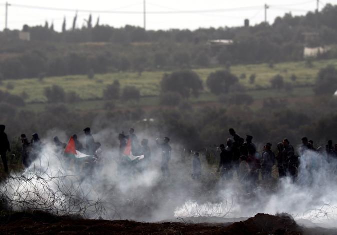 Palestinians protest next to the border fence between Israel and the Gaza Strip, March 30, 201