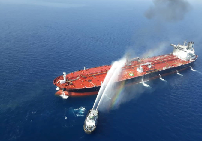 An Iranian navy boat tries to stop the fire of an oil tanker after it was attacked in the Gulf