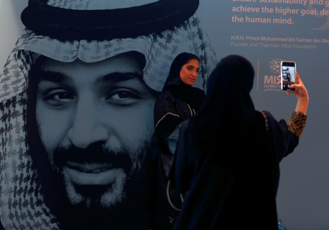 Participants take photos next to a picture of Saudi Crown Prince Mohammed bin Salman during the Mis