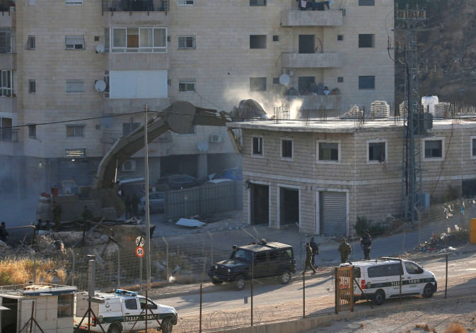 Israeli machinery demolishes a Palestinian building on the outskirts of Jerusalem