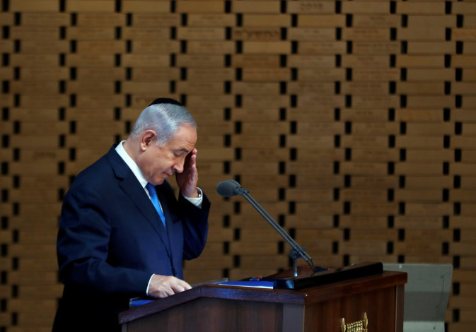Israeli Prime Minister Benjamin Netanyahu gestures as he speaks during a memorial ceremony for Israe