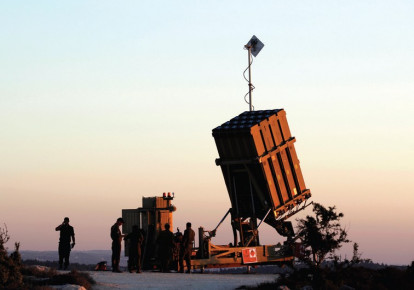 Soldiers stand next to an Iron Dome battery. (photo credit: REUTERS)