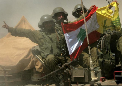 An Israeli armored personnel carrier team shows a Hezbollah and Lebanese flag as they return from fighting near the Israeli village of Avivim, July 25, 2006 (photo credit: REUTERS)