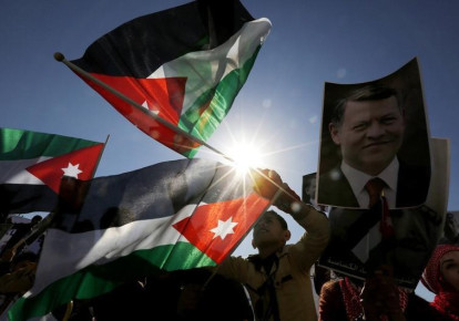 Protesters hold up pictures of Jordanian King Abdullah and pilot Muath al-Kasaesbeh with national flags (photo credit: REUTERS)