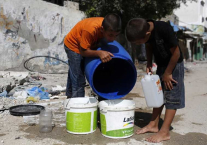 Palestinian children in Gaza fetch water from a container (photo credit: REUTERS)
