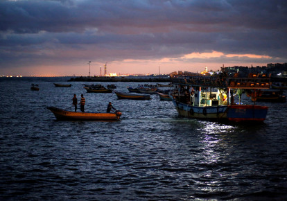 Palestinian fishermen ride their boats as they return from fishing at the seaport of Gaza City (photo credit: REUTERS/MOHAMMED SALEM)