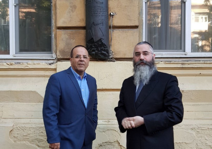 Communications Minister Ayoub Kara and Chabad Rabbi Avraham Wolff outside Ze'ev Jabotinsky's home with a Mezuzah-shaped plaque marking the spot. (photo credit: Courtesy)