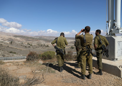 Israeli forces are seen near a border fence between the Israeli side of the Golan Heights and Syria, November 4, 2017. (photo credit: REUTERS)
