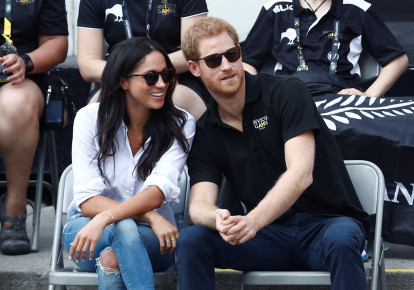 Britain's Prince Harry sits with fiance, actress Meghan Markle to watch a wheelchair tennis event during the Invictus Games (photo credit: MARK BLINCH/ REUTERS)