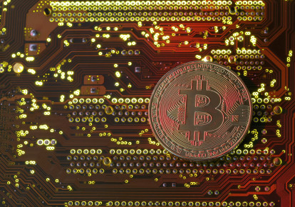 A copy of bitcoin standing on PC motherboard is seen in this illustration picture (photo credit: REUTERS/ DADO RUVIC)