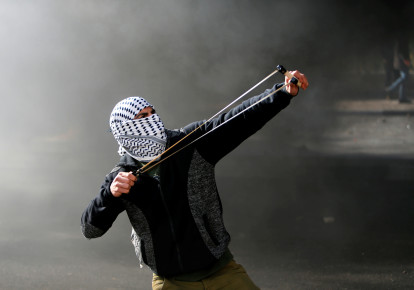 "A Palestinian protester uses a sling shot to hurl stones towards Israeli troops during clashes as Palestinians call for a ""day of rage"" in response to US President Donald Trump's recognition of Jerusalem as Israel's capital, in the West Bank city of Bethlehem December 8, 2017. (photo credit: MUSSA QAWASMA / REUTERS)"