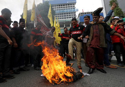Pro-Palestine protesters burn an effigy of U.S. President Donald Trump as they march towards the US embassy in Kuala Lumpur, Malaysia (photo credit: STRINGER/ REUTERS)