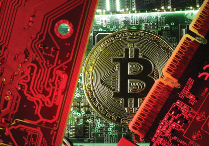 A coin representing the bitcoin cryptocurrency is seen on computer circuit boards in this illustrative picture (photo credit: REUTERS)