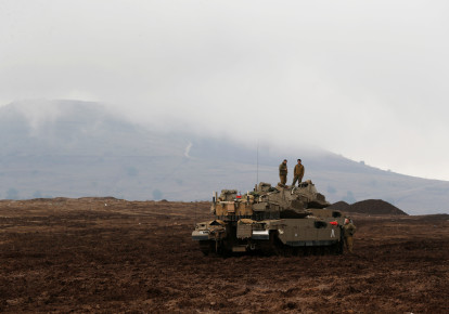 Israeli soldiers stand atop tanks in the Israeli Golan Heights, close to Israel's frontier with Syria November 22, 2017 (photo credit: REUTERS/AMMAR AWAD)