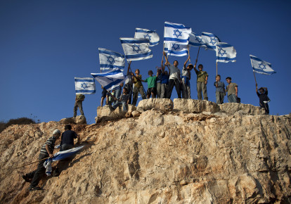 Jewish youth hold Israeli flags at the beginning of a rally march in the West Bank settlement of Itamar, near Nablus. (photo credit: NIR ELIAS / REUTERS)