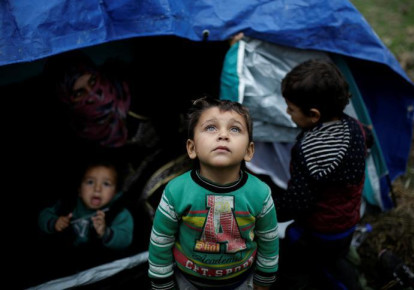 A Syrian refugee boy stands in front of his family tent at a makeshift camp for refugees and migrants next to the Moria camp on the island of Lesbos, Greece (REUTERS/Alkis Konstantinidis (photo credit: ALKIS KONSTANTINIDIS / REUTERS)