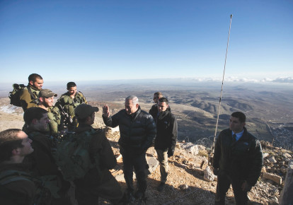 PRIME MINISTER Benjamin Netanyahu chats with Israeli soldiers at a military outpost during a visit to Mount Hermon in the Golan Heights overlooking the Israel-Syria border in 2015. (photo credit: REUTERS/BAZ RATNER)