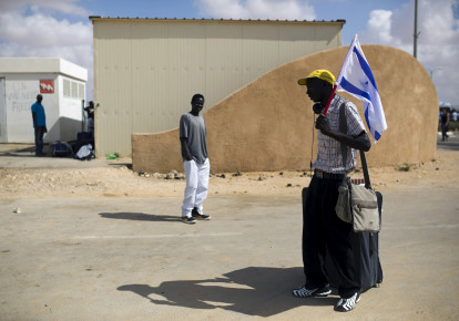 An African migrant holds an Israeli flag after being released from Holot detention centre in Israel's southern Negev desert August 25, 2015. (photo credit: REUTERS/AMIR COHEN)