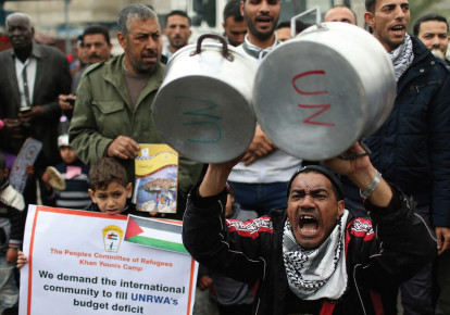 Palestinains take part in a protest against aid cuts, outside the United Nations' offices in Khan Yunis in the southern Gaza Strip. (photo credit: IBRAHEEM ABU MUSTAFA / REUTERS)