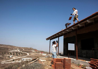 Men work on the roof of a house under construction in the outpost of Havat Gilad, south of the West Bank city of Nablus, November 5, 2013. REUTERS/Nir Elias/File Photo (photo credit: REUTERS/NIR ELIAS)