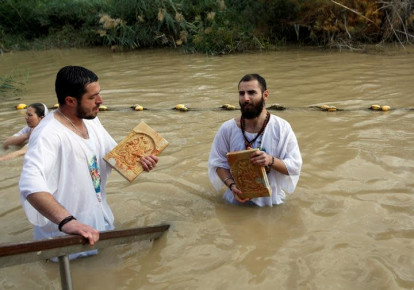 Christian pilgrims dip in the waters of the Jordan River during a baptism ceremony at the Qasr el-Yahud site, near Jericho, in January. (photo credit: MUSSA QAWASMA / REUTERS)