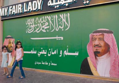 GIRLS STAND next to a poster depicting Saudi Arabia's King Salman bin Abdulaziz Al Saud (right) and Crown Prince Mohammed bin Salman in Jeddah, Saudi Arabia, 2017.  (photo credit: REUTERS/REEM BAESHEN)