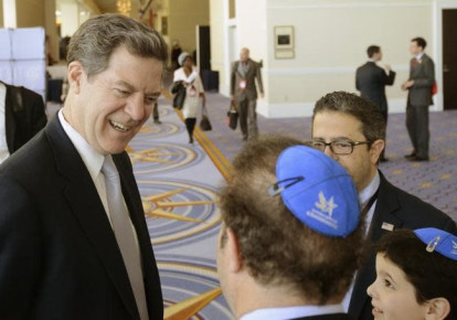 Then-Kansas Gov. Sam Brownback chats with a group from the Young Jewish Conservatives at the Conservative Political Action Conference in Maryland in 2015 (photo credit: MIKE THEILER/REUTERS)