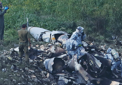 SECURITY PERSONNEL examine the remains of an Israel Air Force F-16 fighter plane near Kibbutz Harduf on February 10, 2018. (Ronen Zvulun/Reuters) (photo credit: RONEN ZVULUN/REUTERS)