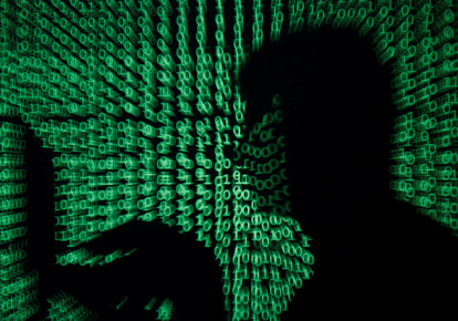 A man holds a laptop computer as cyber code is projected on him (photo credit: KACPER PEMPEL/REUTERS)