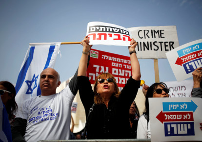 Protesters hold signs as they take part in a rally calling upon Israeli Prime Minister Benjamin Netanyahu to step down in Tel Aviv, Israel February 16, 2018. (photo credit: REUTERS/AMIR COHEN)