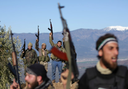 Turkish-backed Free Syrian Army fighters react as they hold their weapons near the city of Afrin, Syria February 19, 2018. (photo credit: REUTERS)