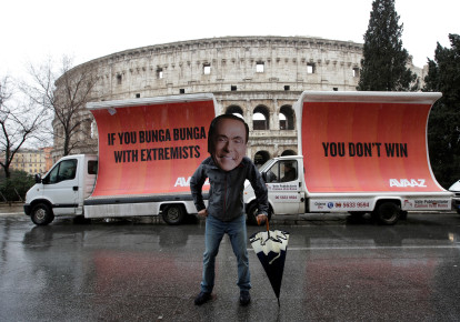 An activist wears a cutout of Silvio Berlusconi a day after Italy's elections, March 2018 (photo credit: MAX ROSSI / REUTERS)