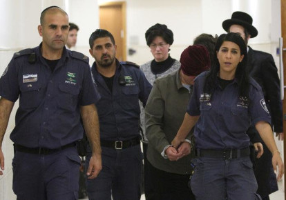 Malka Leifer, a former Australian school principal who is wanted in Australia on suspicion of sexually abusing students, walks in the corridor of the Jerusalem District Court accompanied by Israeli Prison Service guards, in Jerusalem February 14, 2018. REUTERS/Ronen Zvulun (photo credit: REUTERS/Ronen Zvulun)