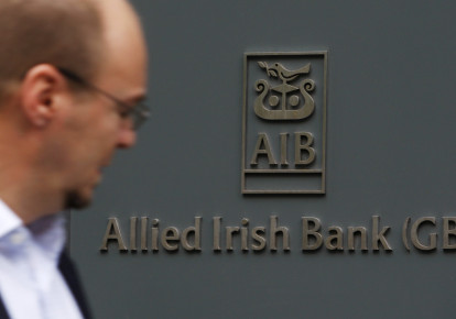 A pedestrian passes a branch of Allied Irish Bank in London (photo credit: REUTERS)