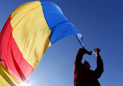 A man waves a Romanian national flag during a march in downtown Bucharest, Romania, October 20, 2013. (photo credit: REUTERS/BOGDAN CRISTEL)