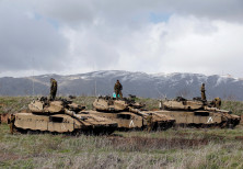 Israeli soldiers stand atop tanks overlooking the border between Israel and Syria