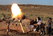 Rebel fighters fire mortar shells towards forces loyal to Syria's President Bashar Assad in Quneitra