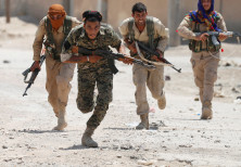 Kurdish fighters from the People's Protection Units (YPG) run across a street in Raqqa, Syria