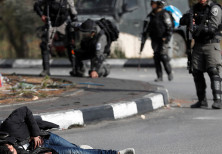Israeli border policemen stand away after shooting a Palestinian man with a knife and what looks lik