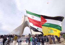 A man carries a giant flag made of flags of Iran, Palestine, Syria and Hezbollah, during a ceremony