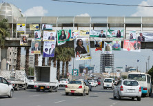 Vehicles drive under campaign posters ahead of the parliamentary election, in Erbil, Iraq