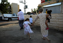 Israelis run for shelter as a siren sounds during a rocket attack at the southern city of Sderot Jul