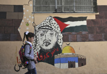 A child walks in front of a mural painting depicting the late Palestinian leader Yasser Arafat on he