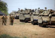 Israeli soldiers speak next to tanks as military armoured vehicles gather in an open area near Israe
