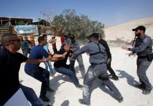 An Israeli policeman grabs an activist in the Palestinian Bedouin village of Khan al-Ahmar in the We