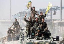 Kurdish-led militiamen ride atop military vehicles as they celebrate victory over Islamic State